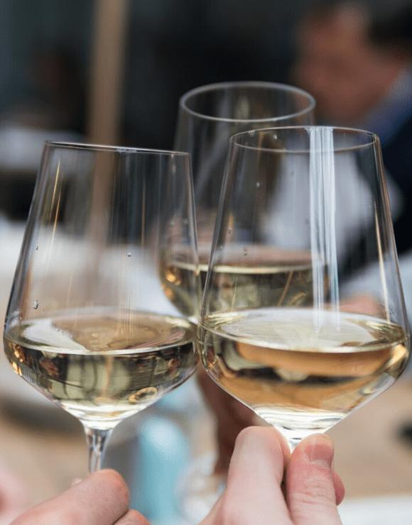 three glasses of white wine being cheered