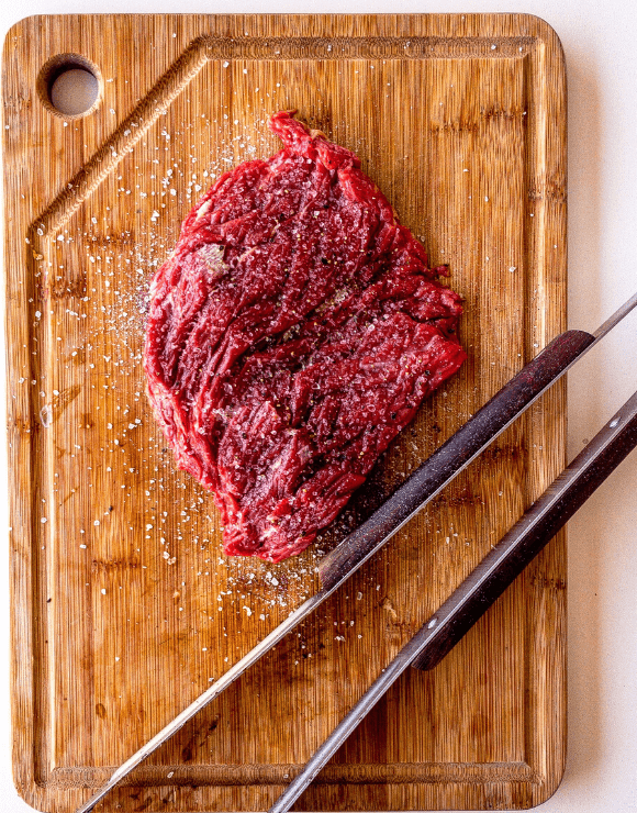 A pound og raw red meat on top of a wooden cutting board