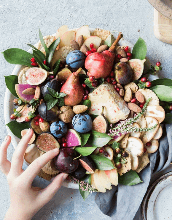 A large round bowl filled with fruit, crackers, nuts, and greens