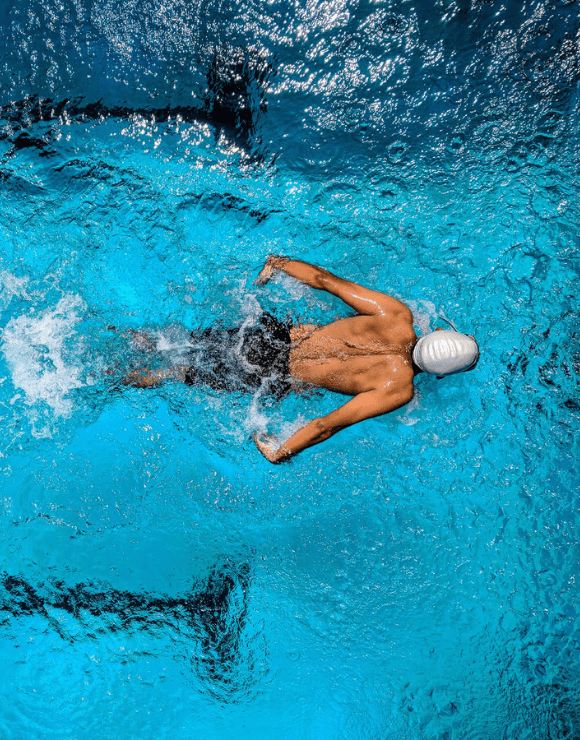 Athletic swimmer breast stroking through the water