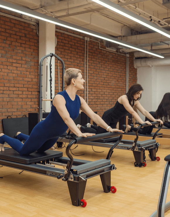 two women in the gym using equipment to help stretch the lower back