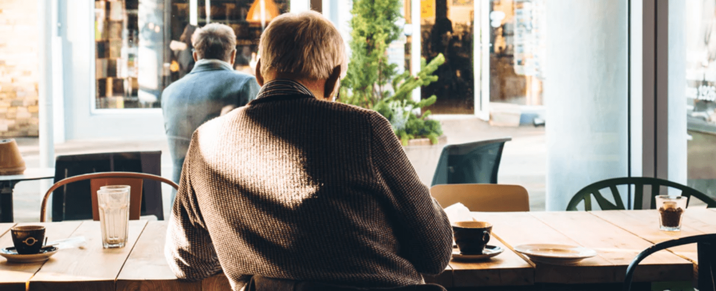 Aging man sitting at a cafe facing out the window