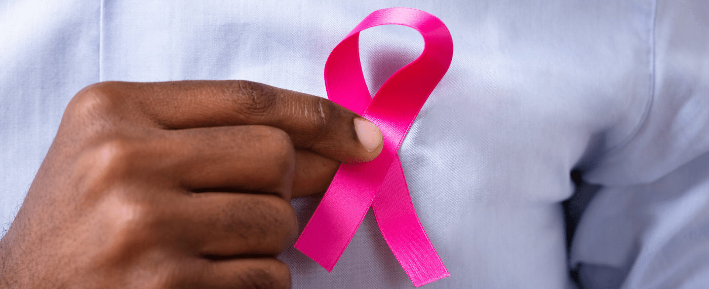 breast cancer ribbon being pinned onto the front of a shirt