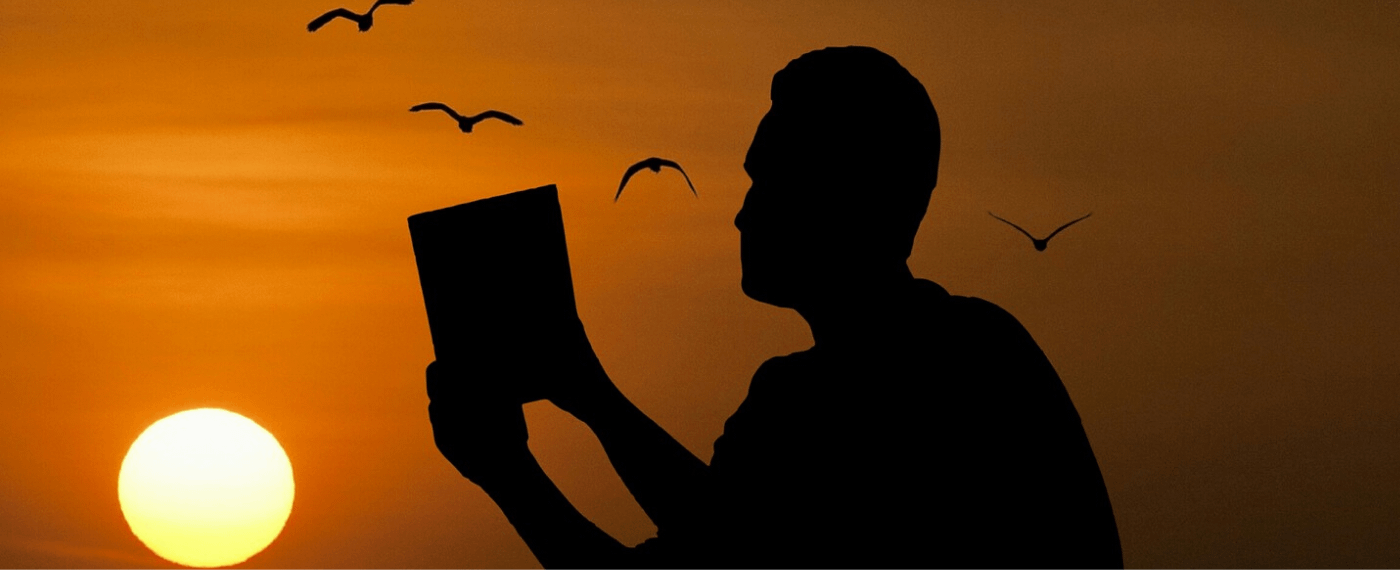 shadow of a man reading a book during sunset