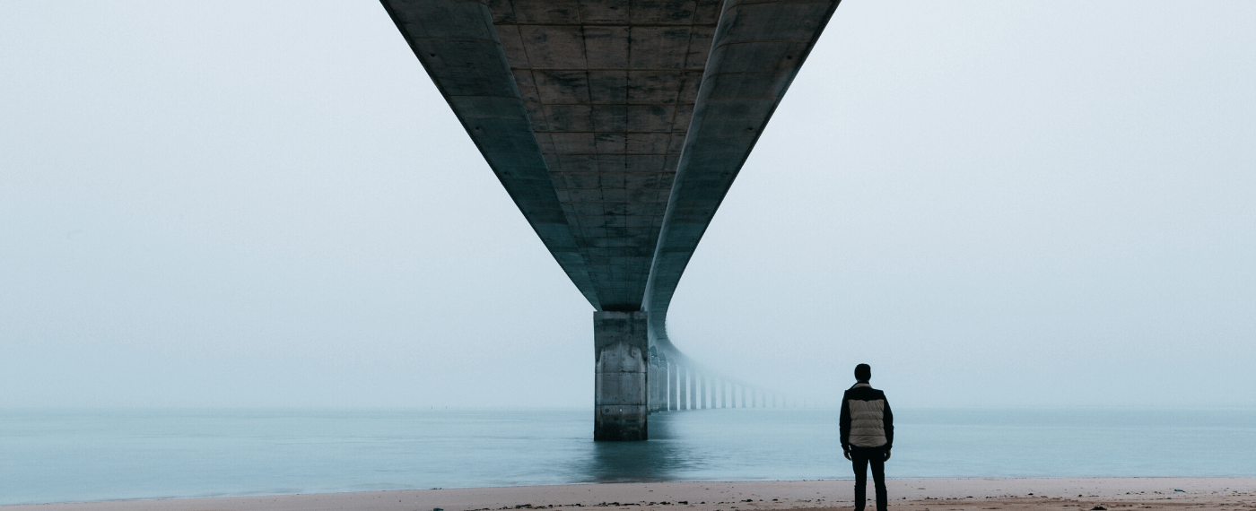 man standing under a bridge by the ocean