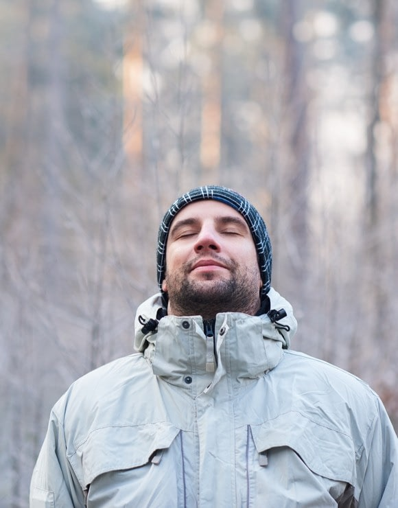 Man in winter gear taking in a deep breathe to relieve holiday stress
