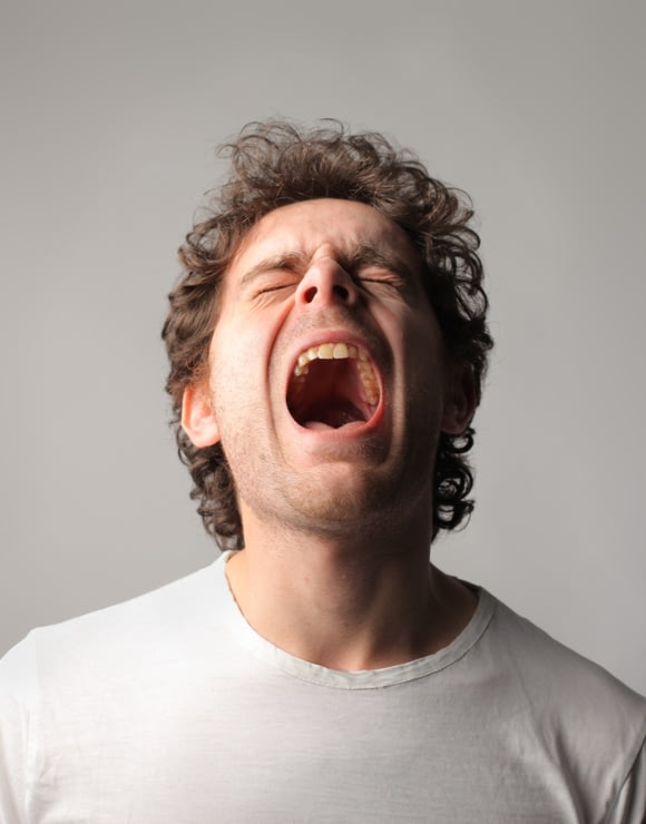 Man leaning head back and yawning largely