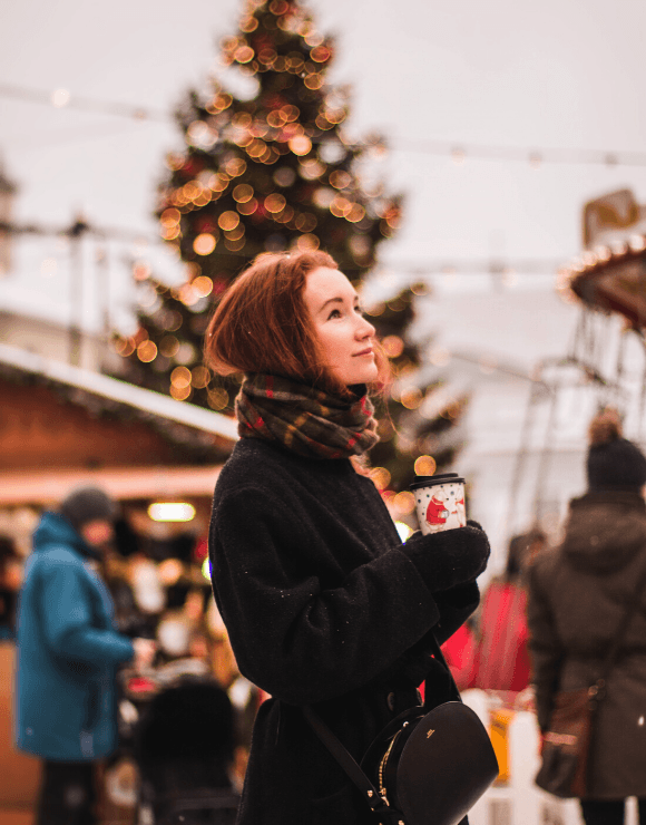 Young girl in winter clothes holding warm coffee to help ease holiday stress