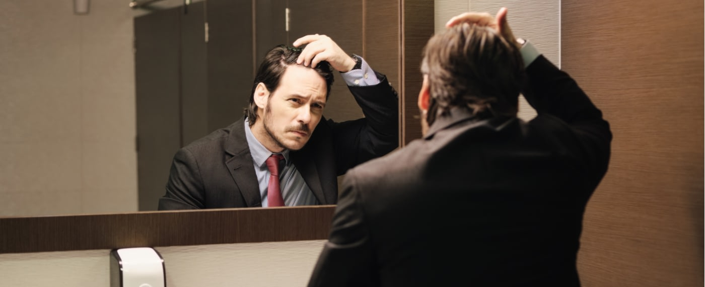 Man in business suit checks his hair line in the bathroom mirror