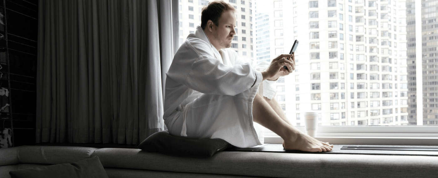 Man in robe sitting by hotel window scrolling through his smartphone