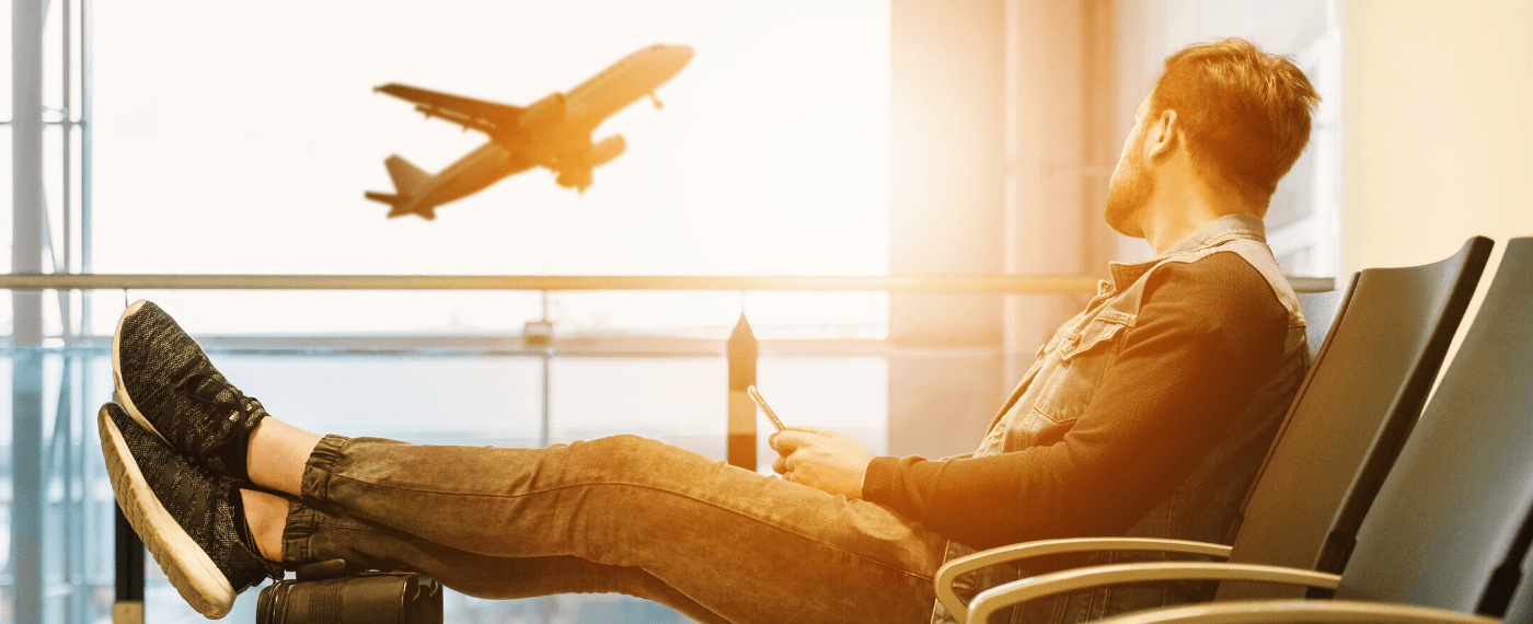 man waiting in airport terminal staring out the window at plane taking off