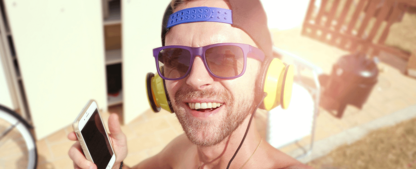 Man with sunglasses smiling listening to music