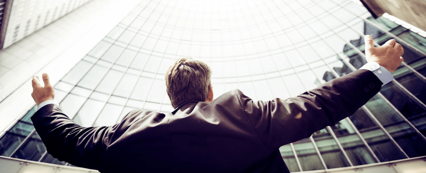 man standing in front of office building with arms raised