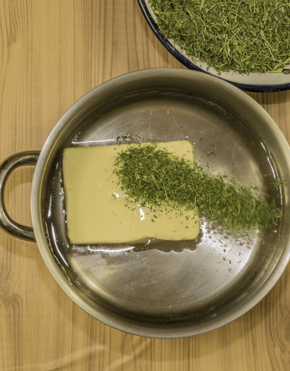 Butter melting and infusing with cannabis in a pan