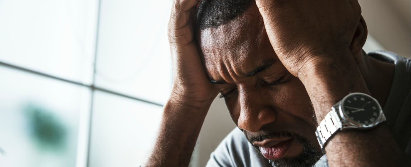 man with obsessive compulsive disorder holding his head