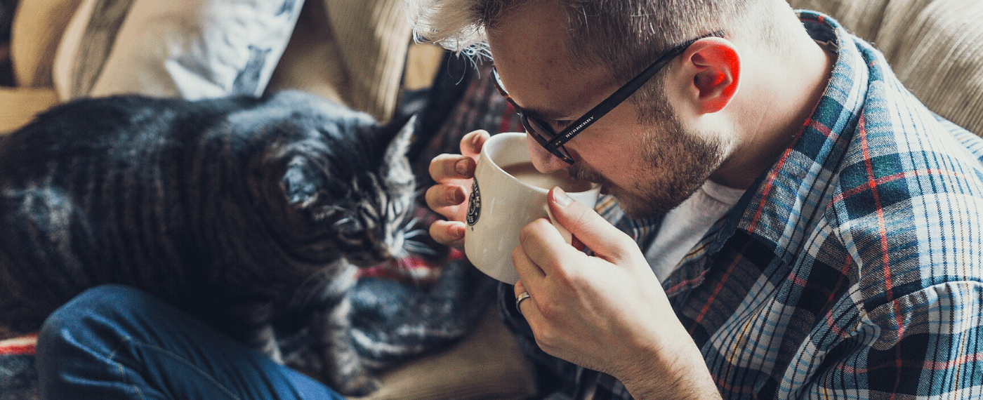 A man sips coffee with his cat, pondering the meaning of self-care