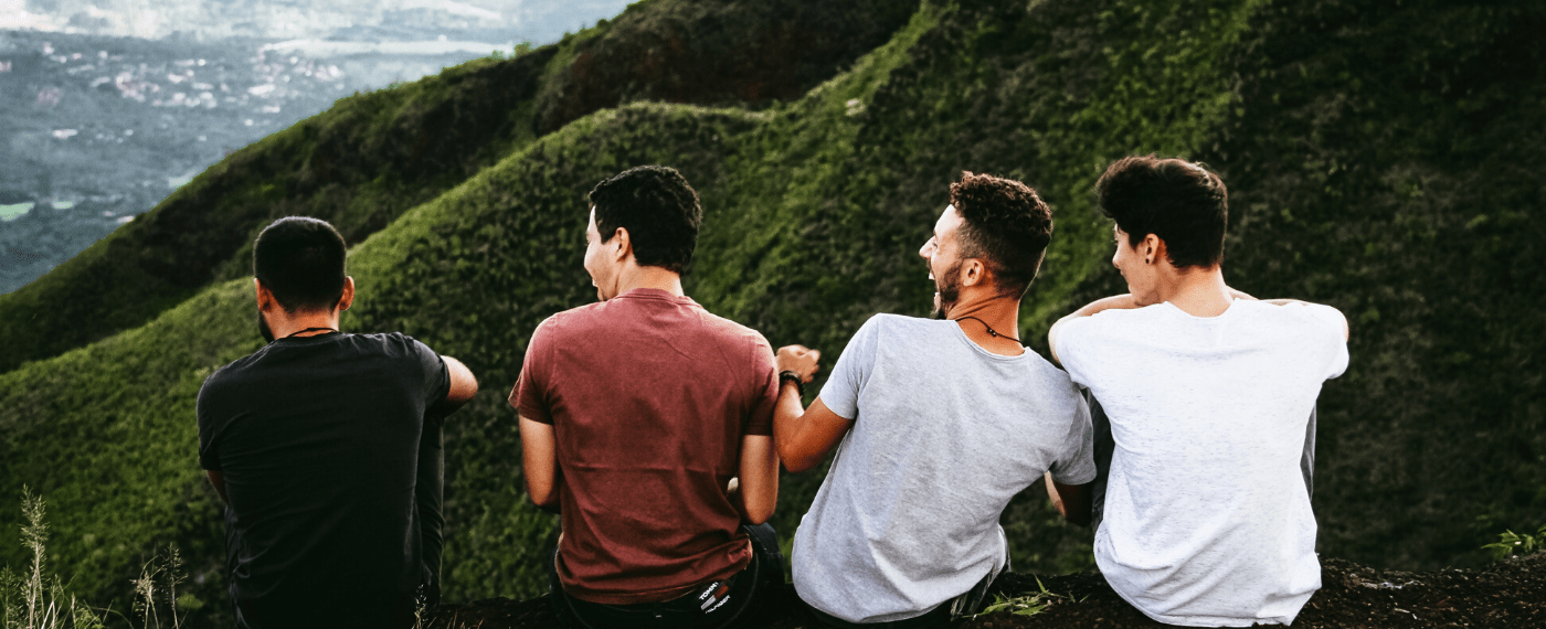 Four male friedns sitting and laughing together on a mountain side