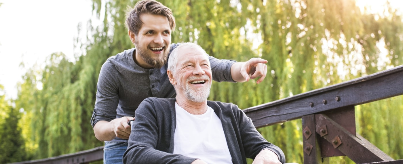 Two men, one young and one old, smile together in a nature setting