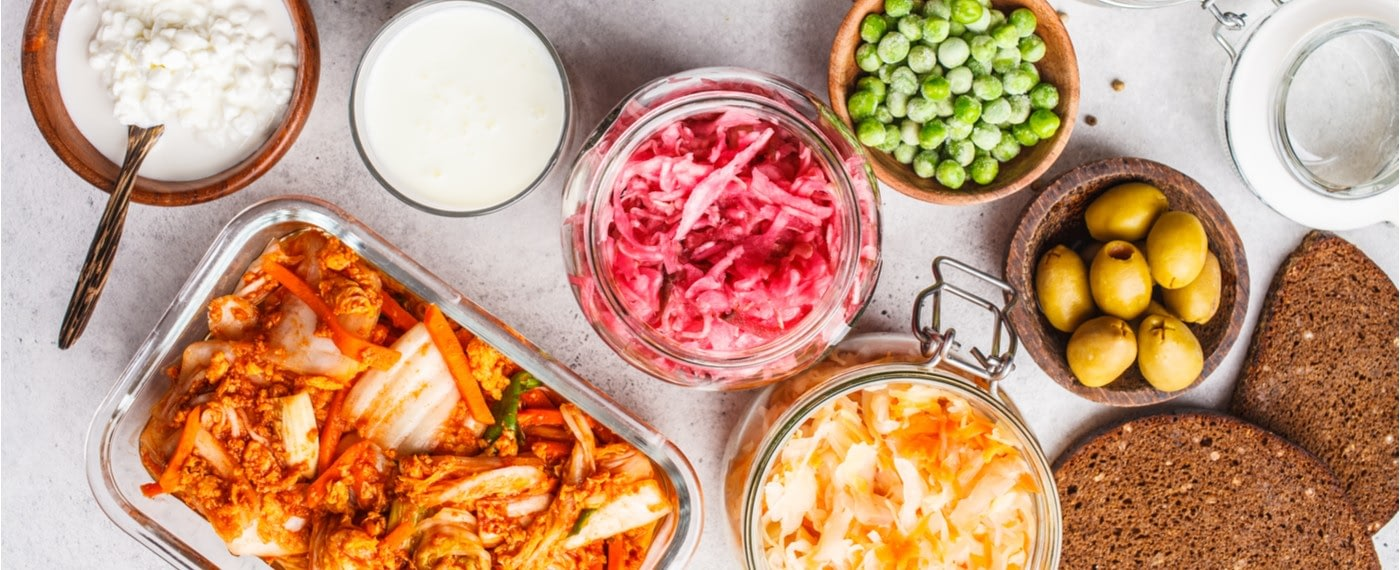 Different types of fermented foods in jars and bowls