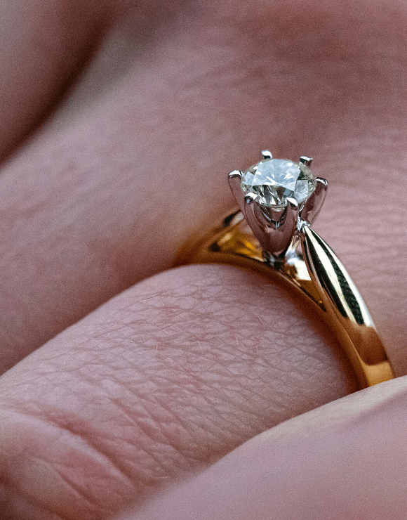 A single diamond wedding ring with a gold band