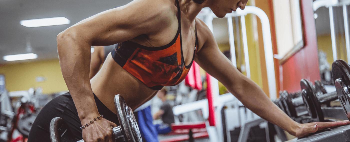Female fitness athlete using dumbbell for back workout