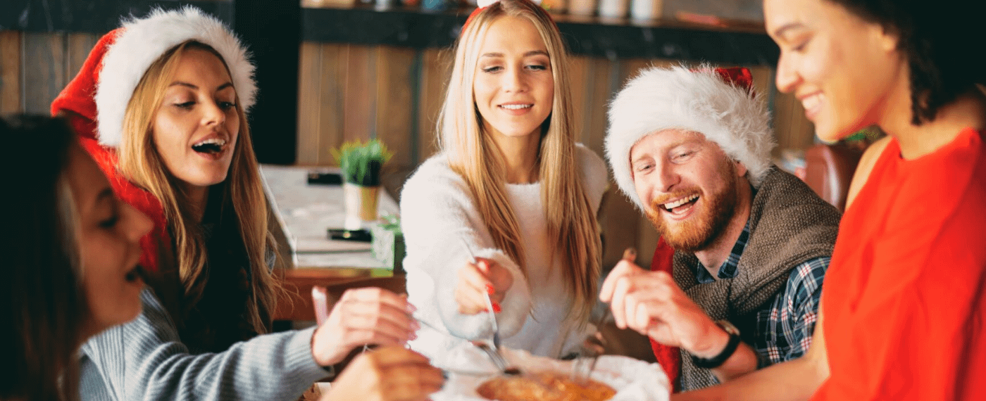Group of friends wearing holiday hats and eating together
