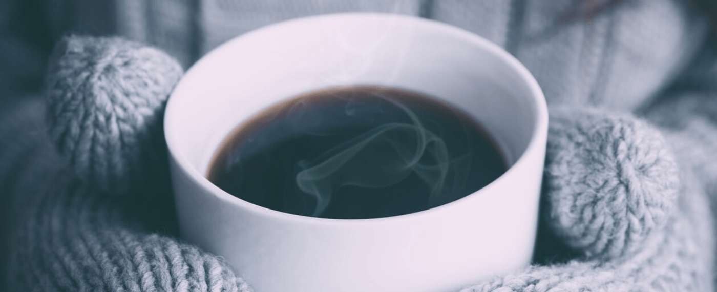A steaming cup and black coffee in a white mug