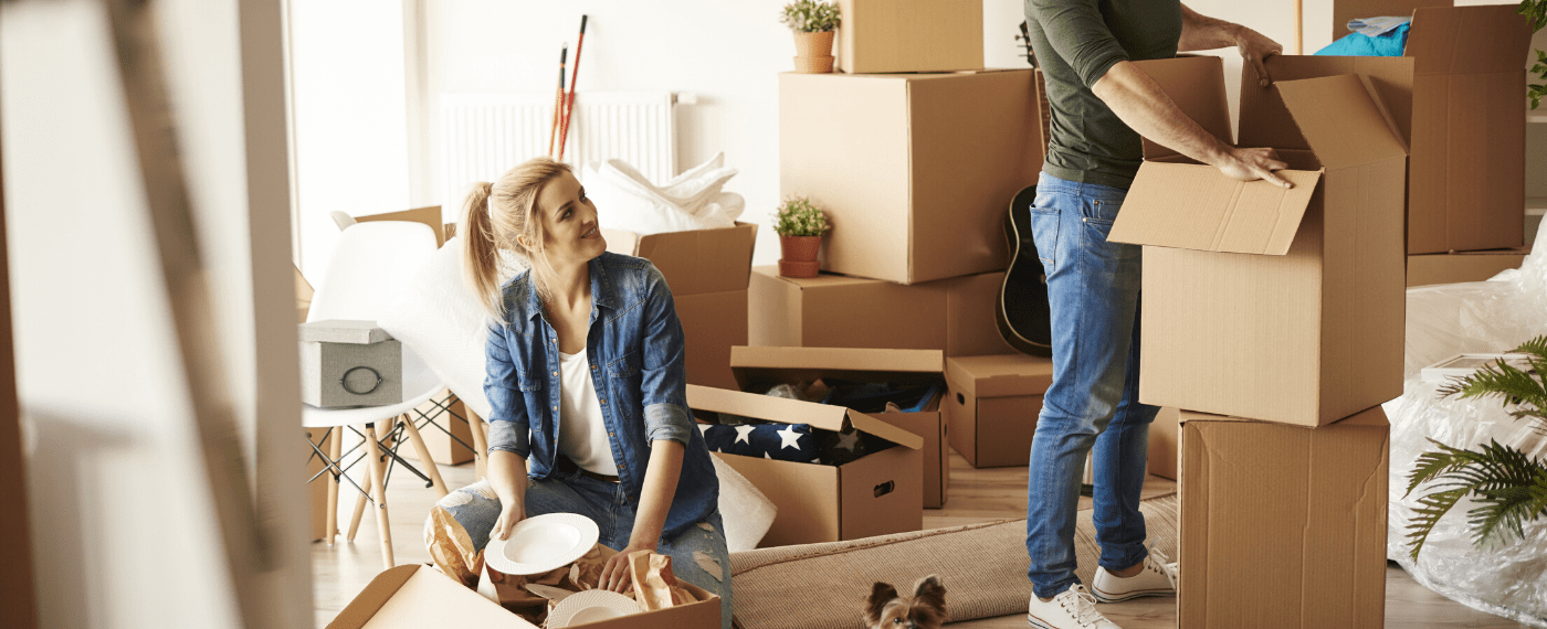 Married couple unpacking boxes after moving into a new home for the New Year