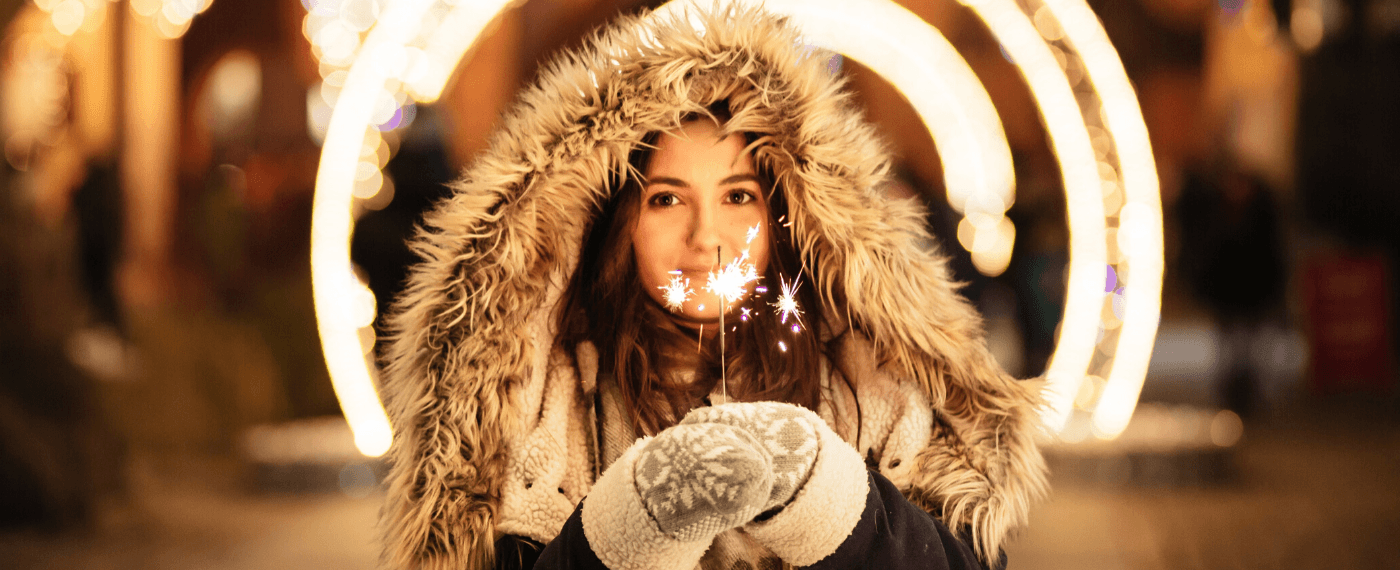 A young girl in a large winter coat holding a lit sparkler