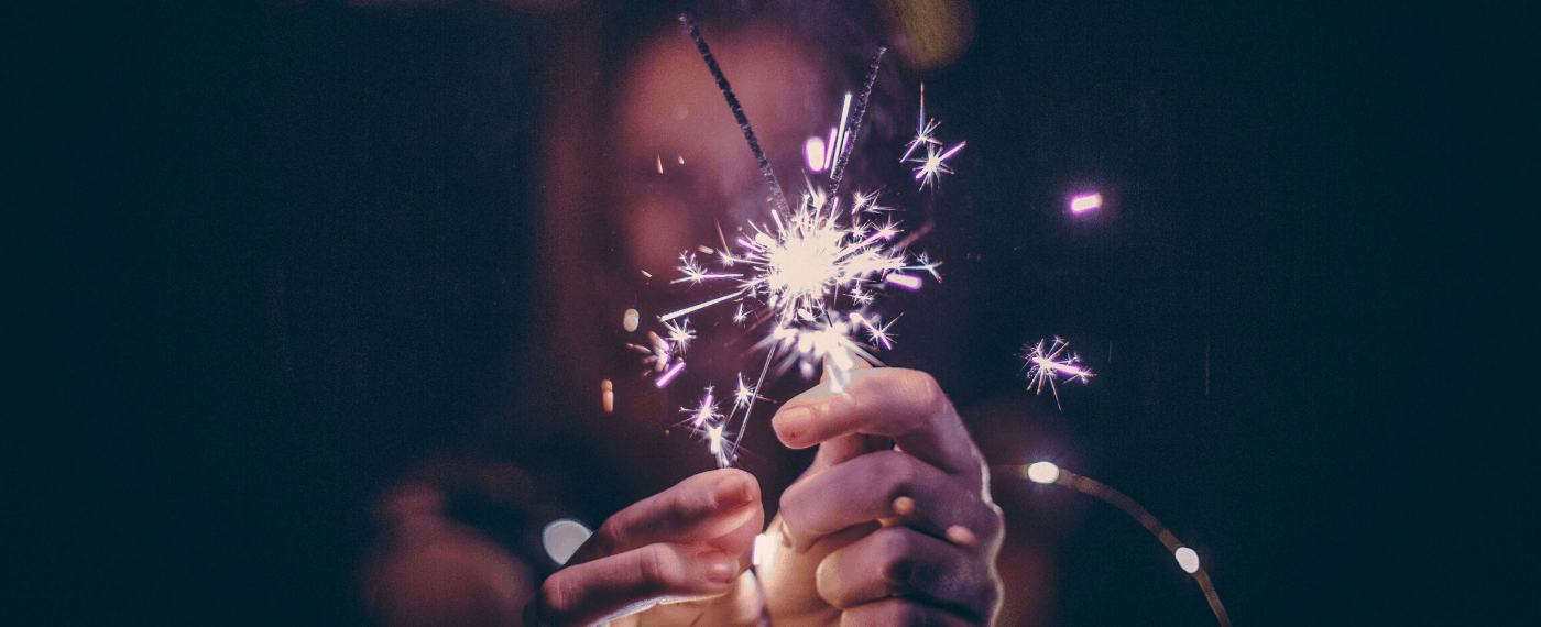 Woman holding two sparklers together creating a bright spark