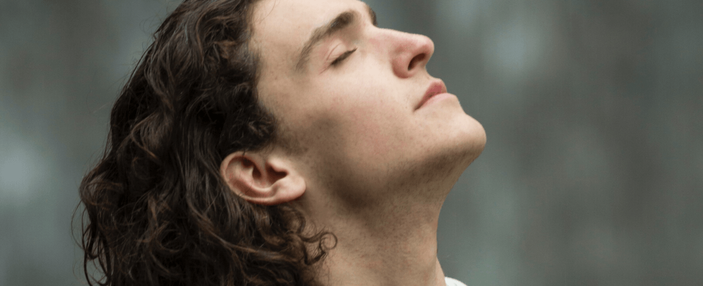 man leaning head back and breathing in fresh air