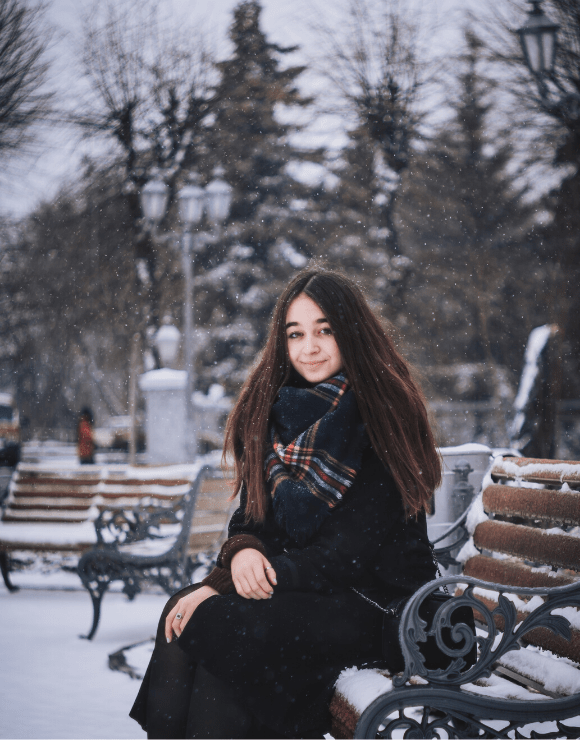 young girl smiling and sitting on snowy park bench