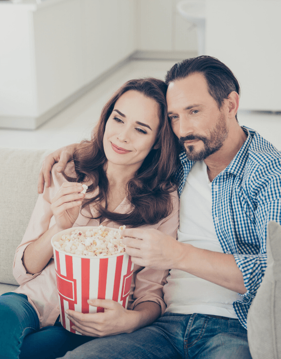 man and woman on couch enjoying a bucket of popcorn