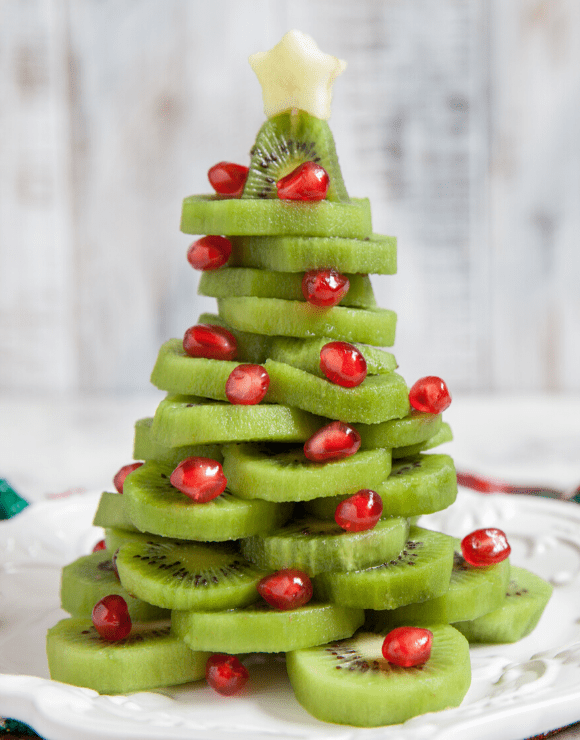 kiwi slices and cranberries arranged into a Christmas tree