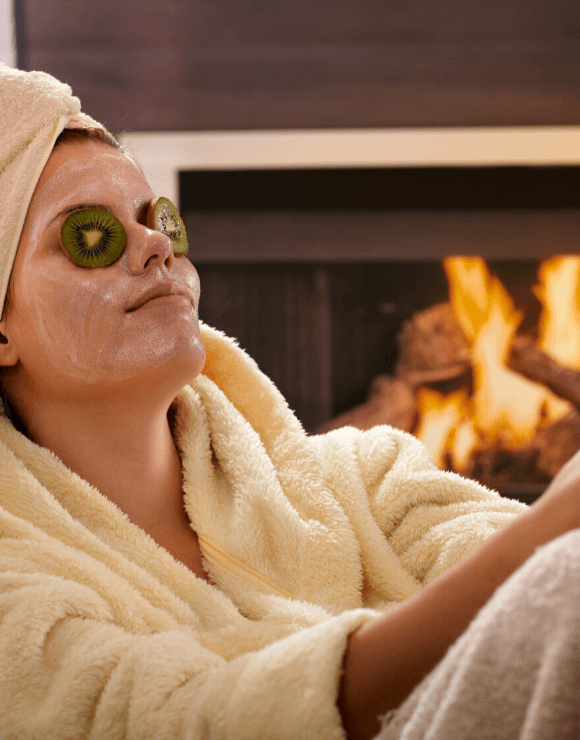 woman in spa robe with cucumber slices on her eyes and a face mask