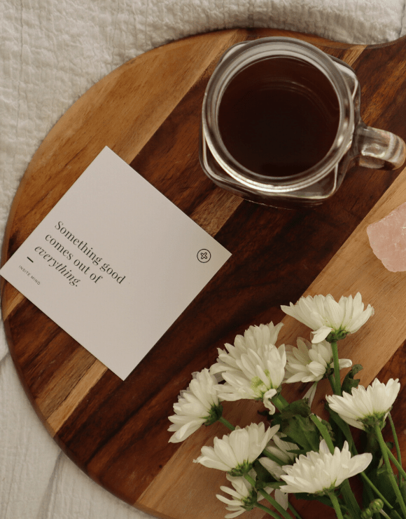 a vase and flowers on a table with a positive note