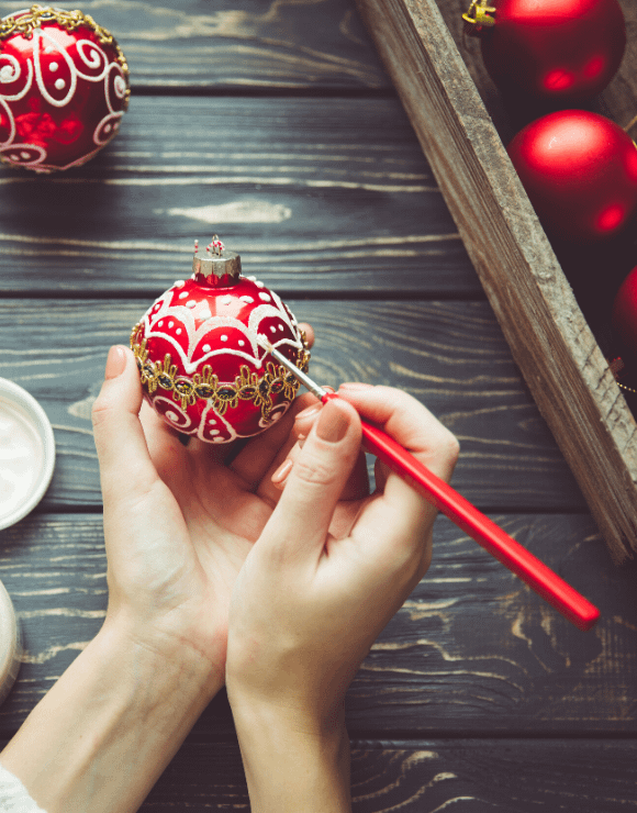 an ornately designed Christmas tree ornament being painted by hand