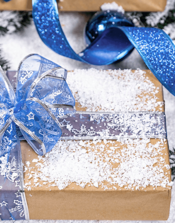 A holiday present wrapped in paper with a ribbon, bow, and snow on top