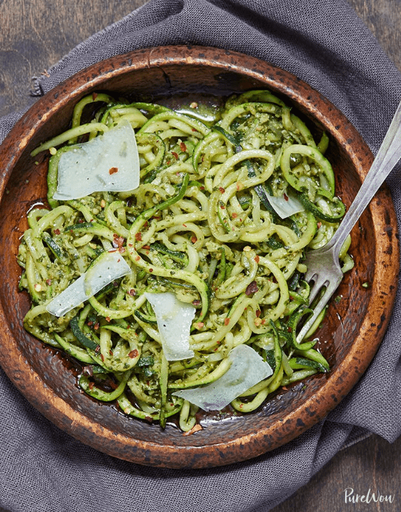 A wooden bowl with pesto zucchini noodles with large slices of parmesan cheese