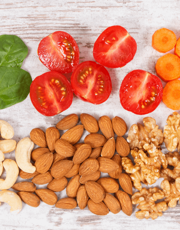 sliced tomatoes next to a pile of different healthy nuts