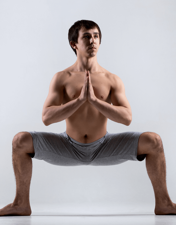 Man practicing the Yoga Squat to help stimulate his gut health