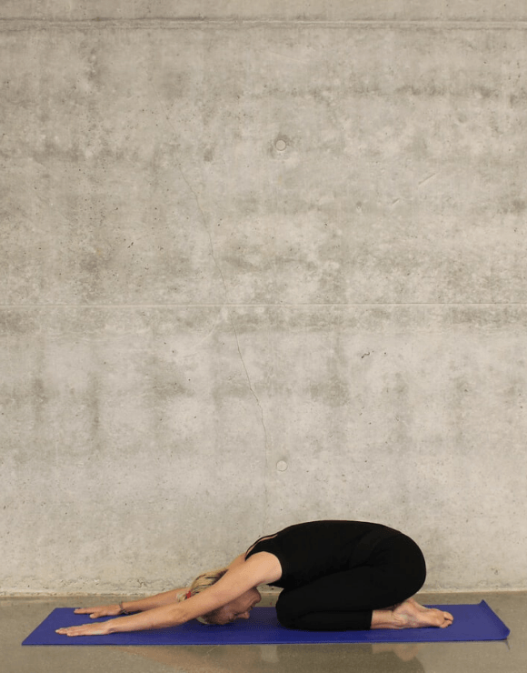 woman stretching on yoga mat with arms out in front of her to help stimulate gut health