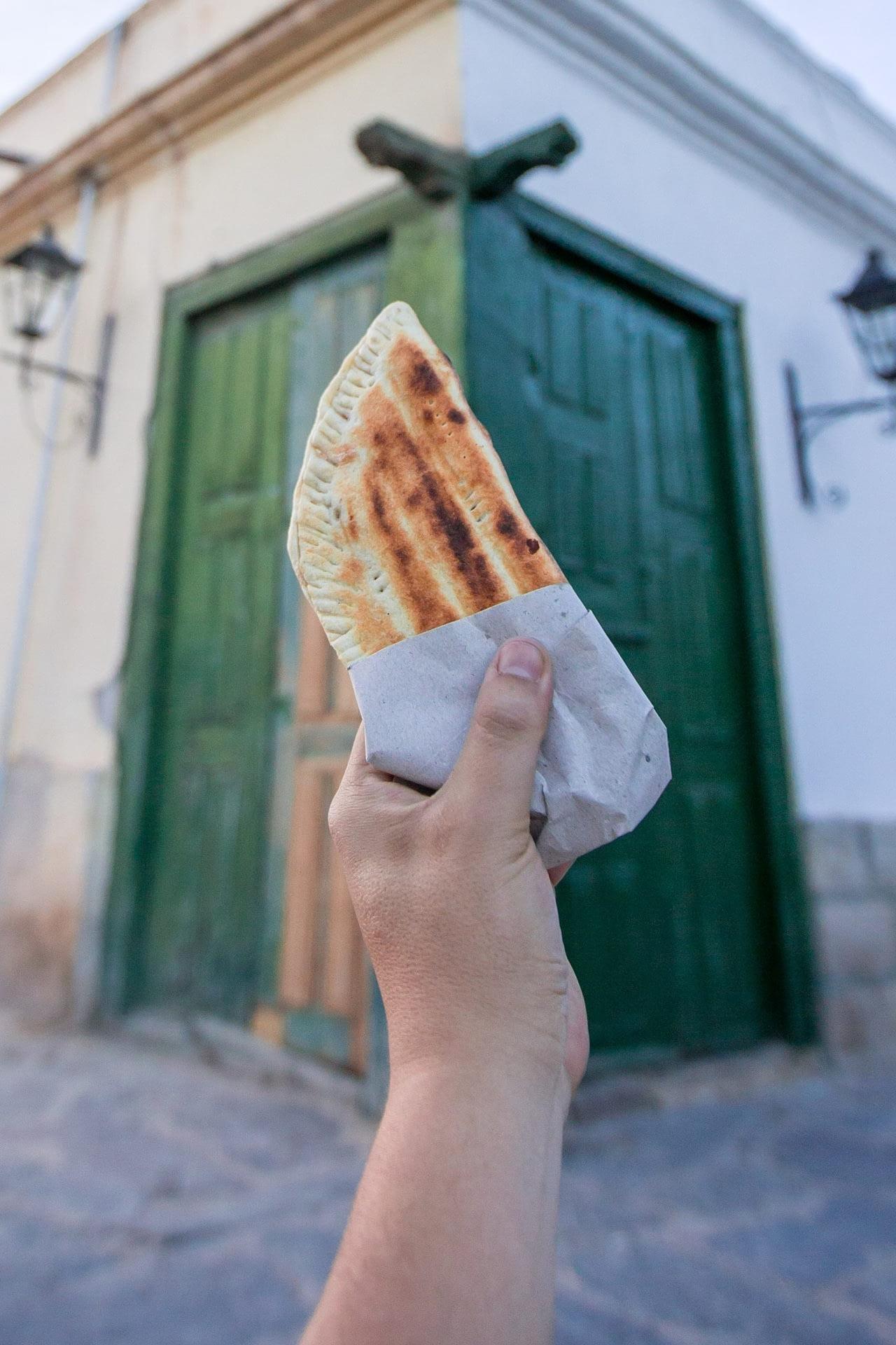 man holding a Argentinian empanada