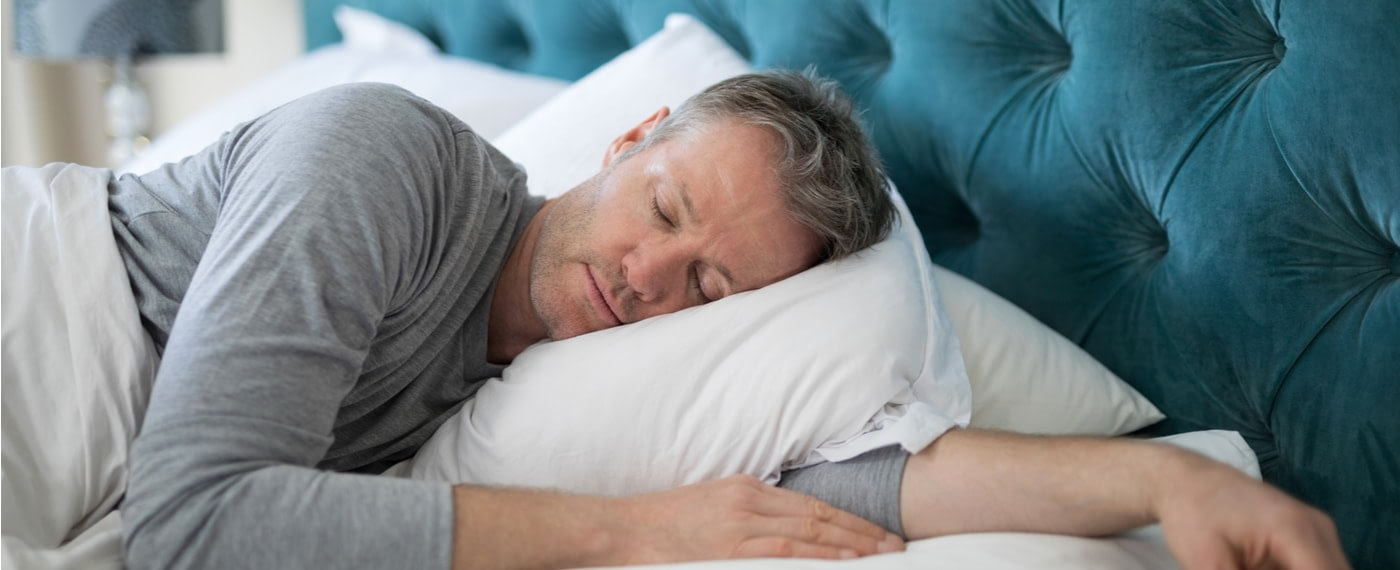 Older male sleeping with one arm under pillow after using natural sleep remedies
