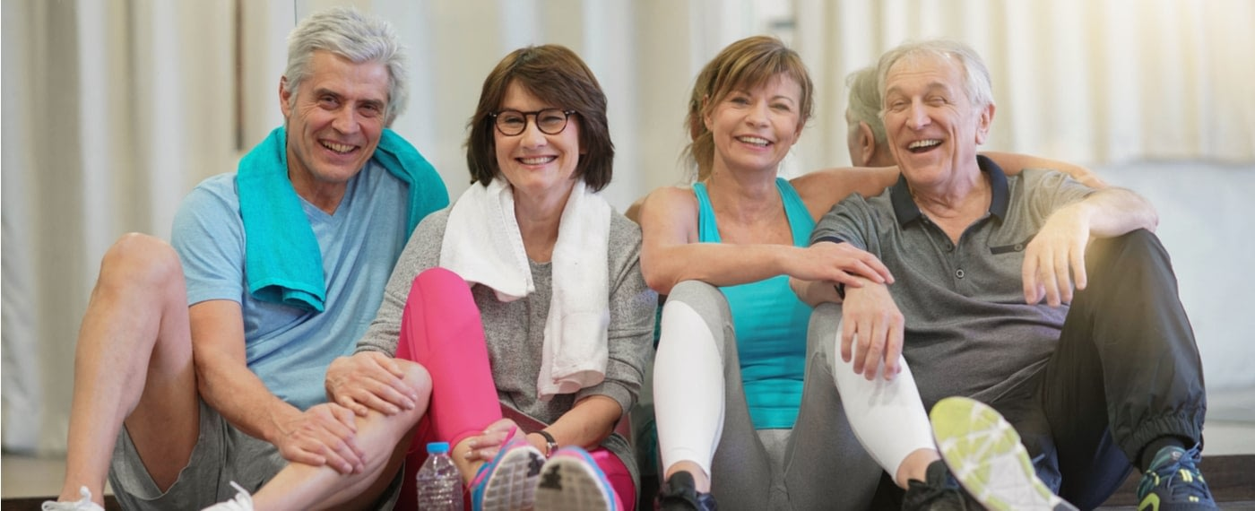 Two older married couples smiling after a yoga for arthritis pain class