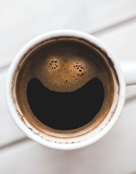 a cup of coffee with the foam forming a smiley face