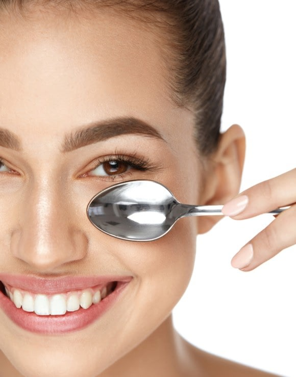 woman applying a cold spoon to her face to help reduce baggy eyes