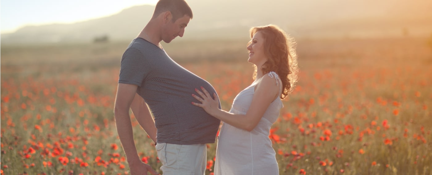 Man experiencing pregnancy belly with pregnant wife