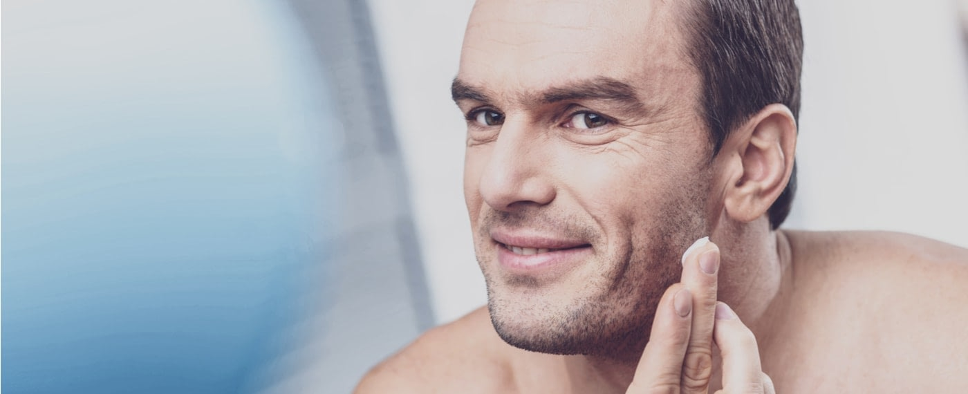 Man applying moisturizer to face to relieve dry skin