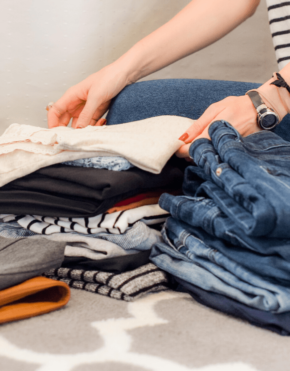 woman folding shirts on top of each other